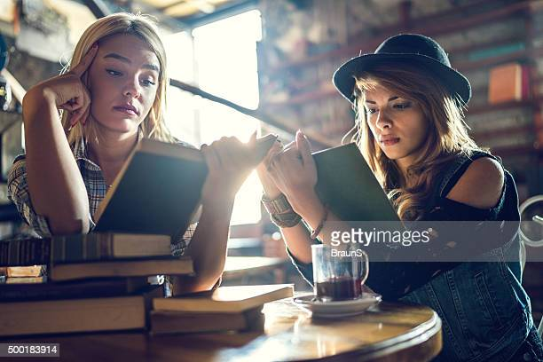 Young women relaxing in a library while studying from books.
