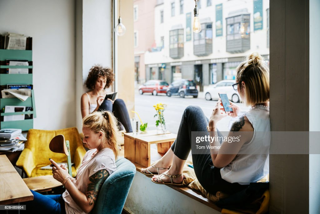 Young Women Relaxing In Cafe Using Their Smartphones : Foto stock