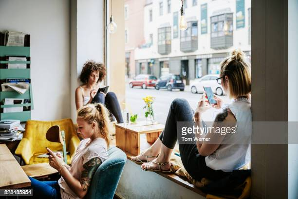 young women relaxing in cafe using their smartphones - leben in der stadt stock-fotos und bilder
