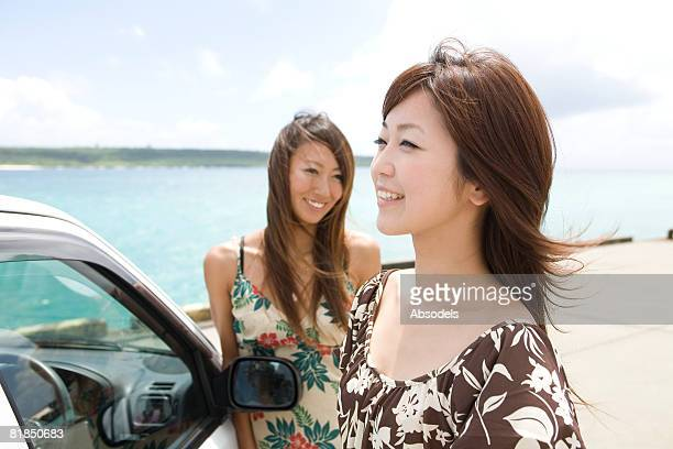 Young women resting outside of car