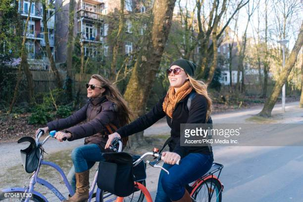 Young women ride bicycles, on residential street