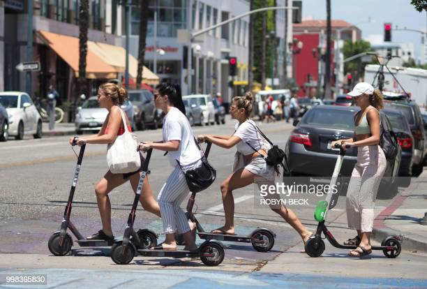 Young women ride shared electric scooters in Santa Monica, California, on July 13, 2018. - Cities across the U.S. Are grappling with the growing...