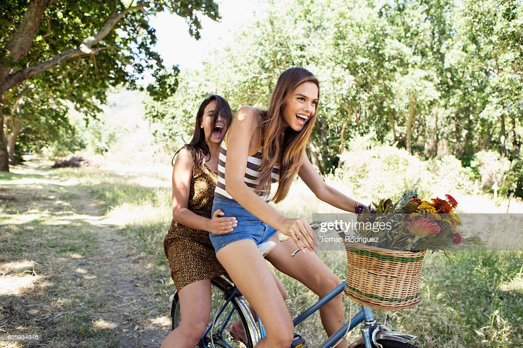 Young women riding bicycle together : Stockfoto