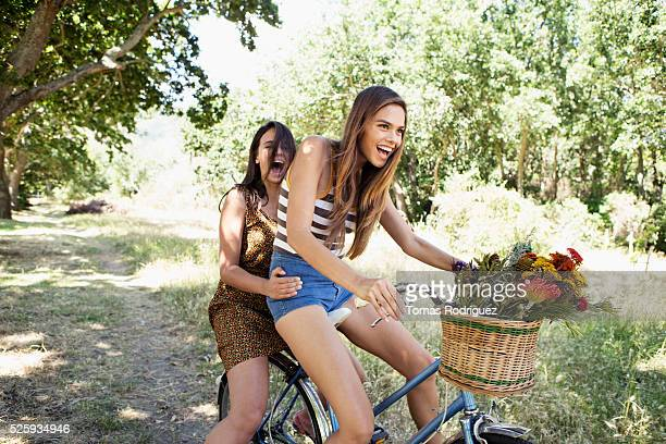 Young women riding bicycle together