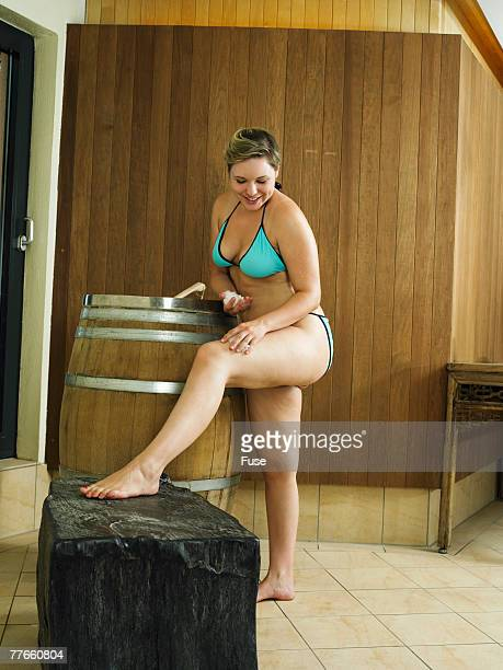 young women rubbing their legs with sea salt - chubby legs stock photos and pictures