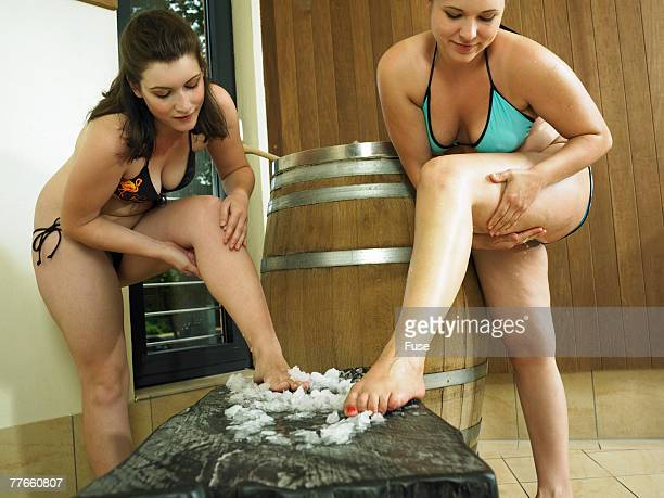 Young Women Rubbing Their Legs with Sea Salt