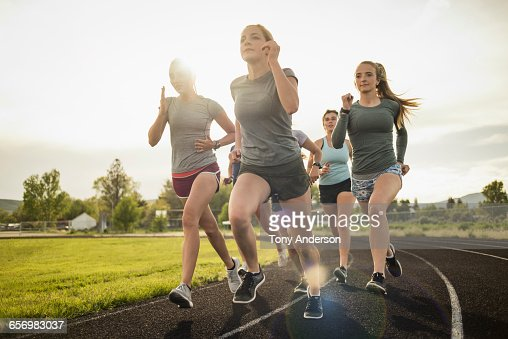 Young women runners rounding turn on track