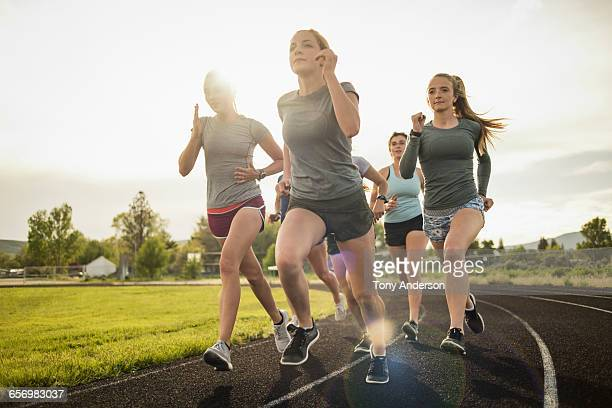 young women runners rounding turn on track - 勝負 ストックフォトと画像
