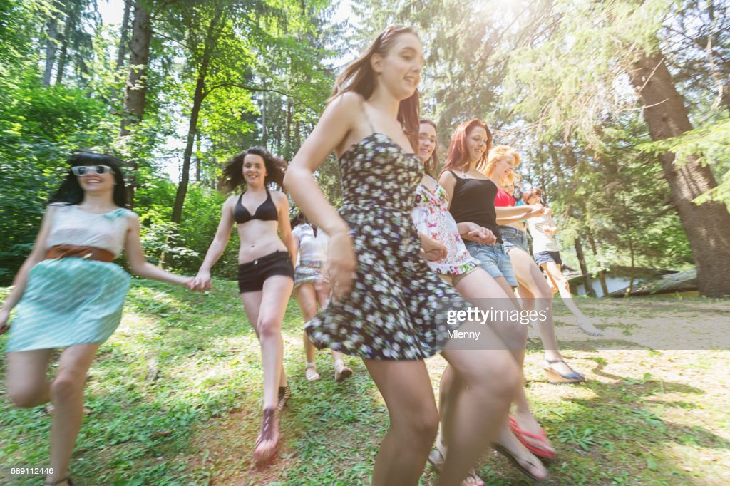 Young women running down green hill towards lake in summer : Stock Photo