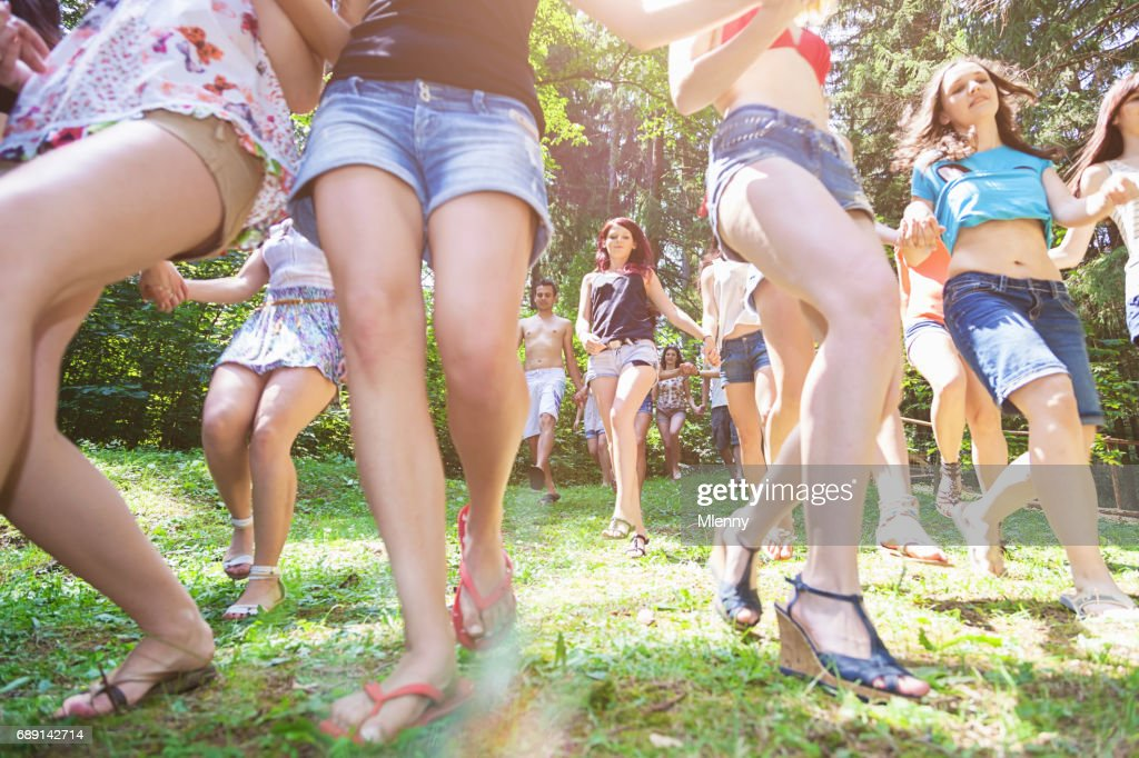 Young women running down hill towards lake in summer : Stock Photo