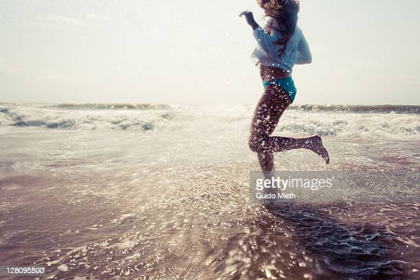 Young women running into sea