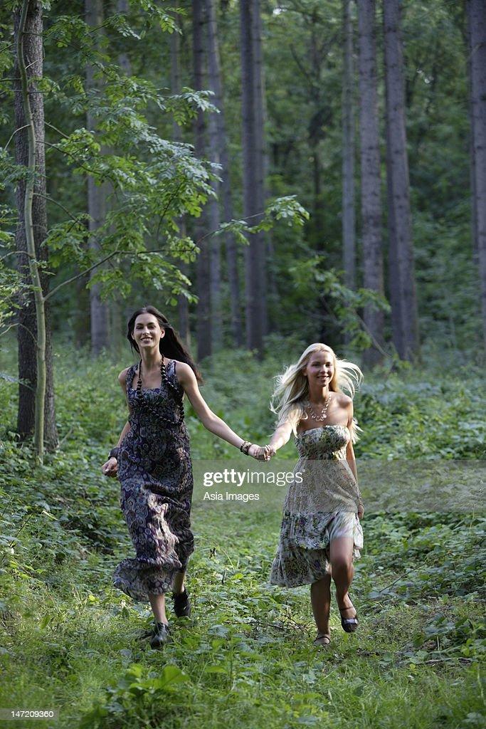 Young women running through forest : Foto de stock