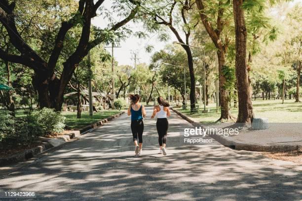 jóvenes corriendo juntos en el parque - parque natural fotografías e imágenes de stock