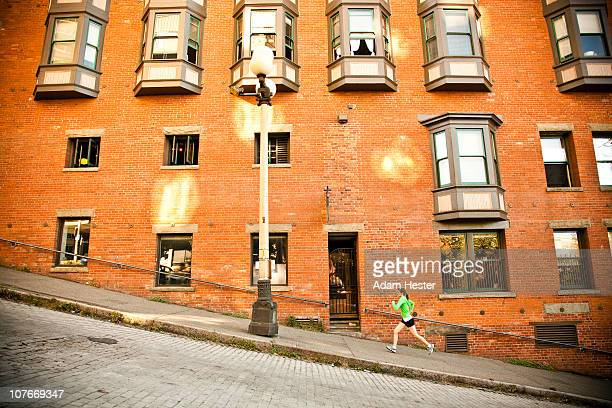 A young women running up a hill in an urban area.