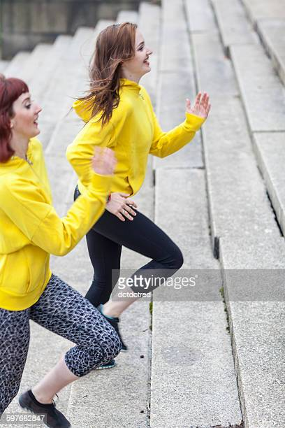 Young women running up steps