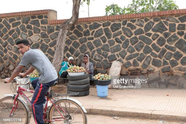 Young women sell fruit on a street A boy is passing by on a bicycle on August 24 2018 in Asmara Eritrea
