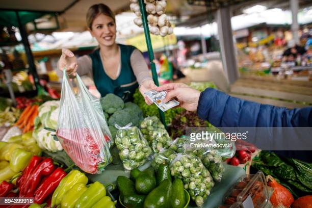 young women selling vegetables at farmer's food market stall. - farmers market stock pictures, royalty-free photos & images