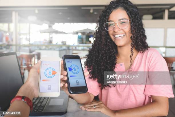 young women sending money through digital wallet, using wireless technology - receiving stock pictures, royalty-free photos & images