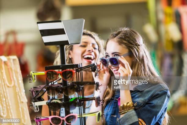 若い女性は、サングラスにしようとして、モールでショッピング - ギフトショップ ストックフォトと画像