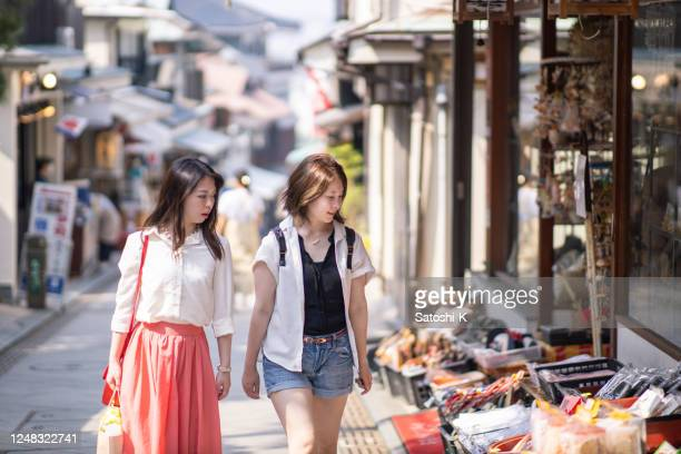 日本の伝統的な商店街で買い物をする若い女性 - ショッピングエリア ストックフォトと画像