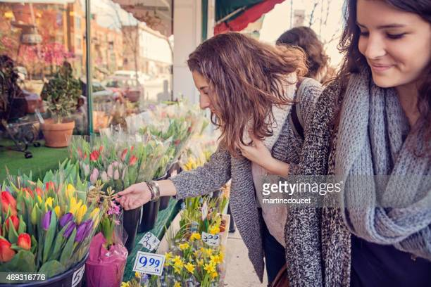 Young women shopping for spring flowers on city sidewalk.