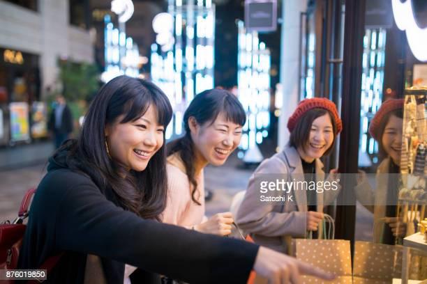 若い女性が夜一緒に買い物 - 30 34歳 ストックフォトと画像