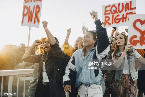 young women shouting while protesting for equal rights against sky - march stock-fotos und bilder