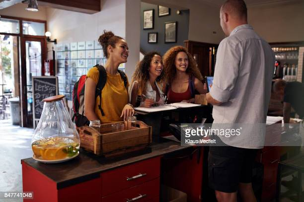 young women signing in to youth hostel - hostel stock pictures, royalty-free photos & images