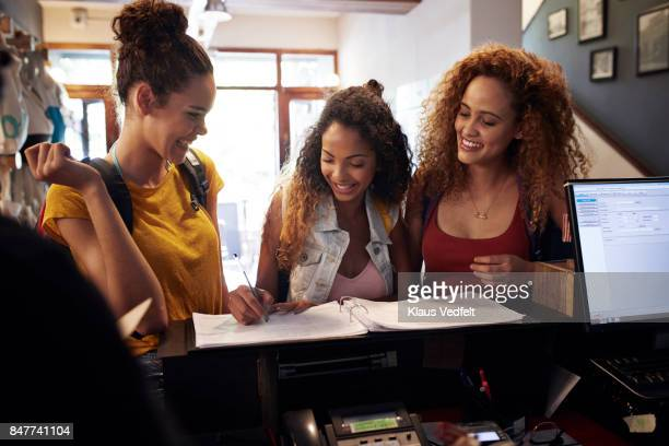 Young women signing in to youth hostel