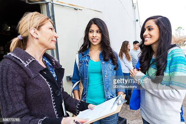 young women signing up to volunteer at community food bank - humanitarian aid stock pictures, royalty-free photos & images
