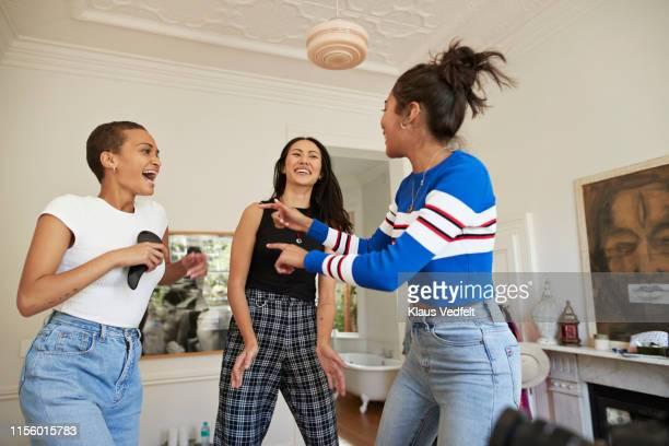 young women singing and dancing in bedroom - pantalones azules fotografías e imágenes de stock