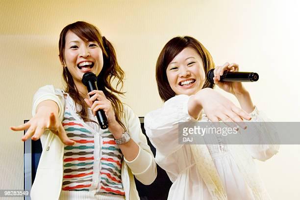 Young women singing karaoke