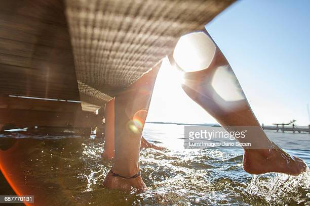 young women sit on pier bathing feet in water - starnberg photos et images de collection