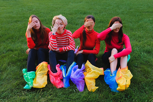 Young women sit on the grass and close their eyes with their hands. On the feet of colored plastic bags - gettyimageskorea