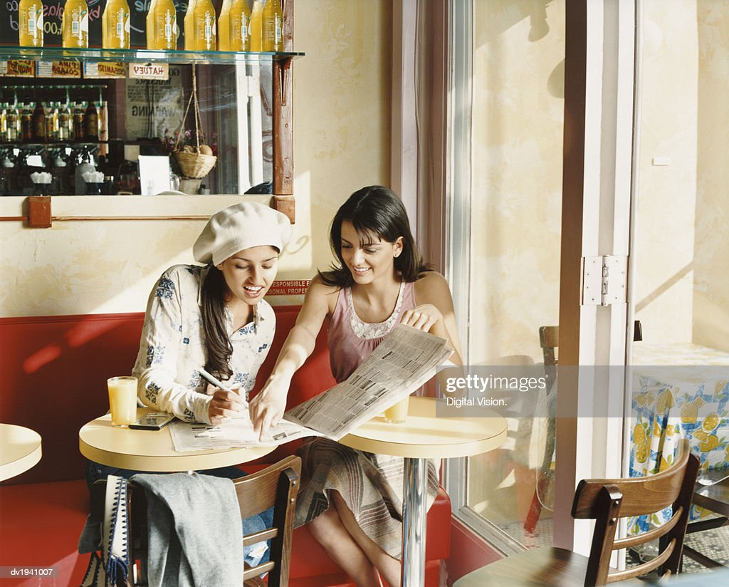 Young Women Sitting in a Cafe Reading a Newspaper : Stock Photo