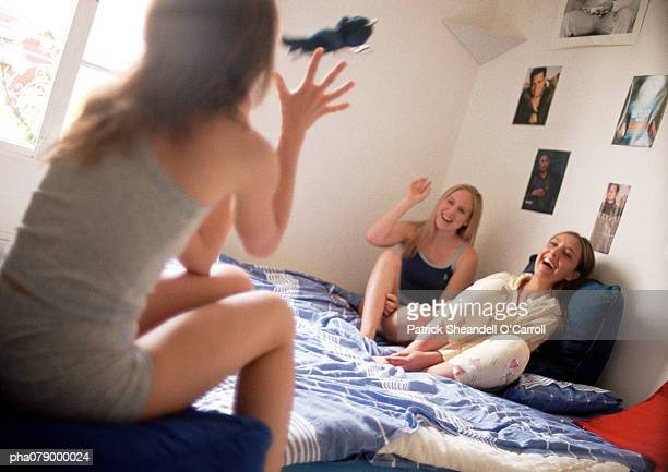 Young women sitting in bedroom talking, laughing.
