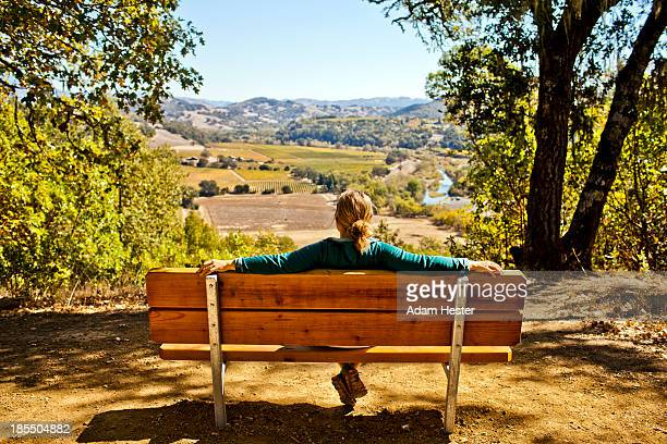 A young women sitting on a bench at a overlook.