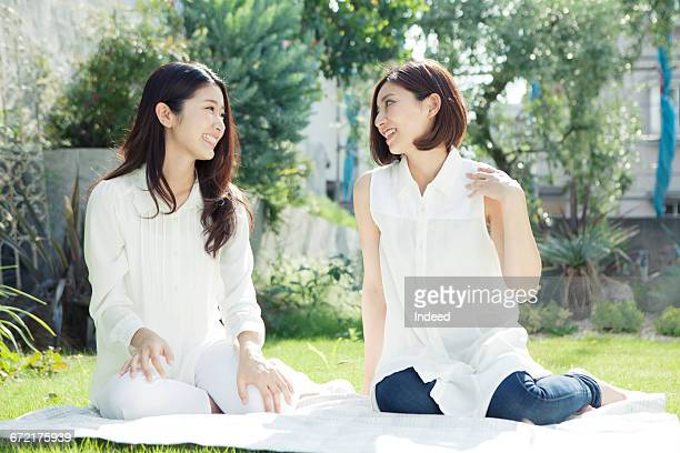 young women sitting on blanket and talking - exclusivamente japonés fotografías e imágenes de stock