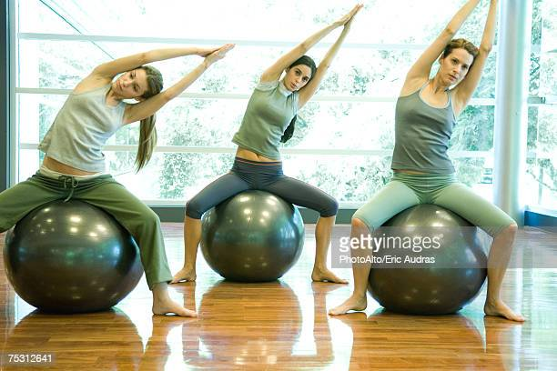 young women sitting on fitness balls, doing side stretch - fitness ball stock pictures, royalty-free photos & images