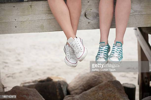 Young women sitting on pier on beach,  low section