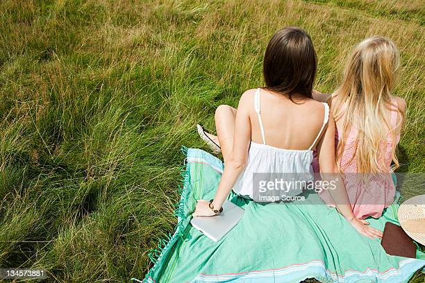 young women sitting together in a field - only young women stock pictures, royalty-free photos & images
