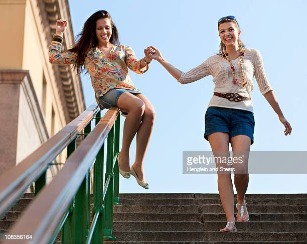 Young women sliding down railing