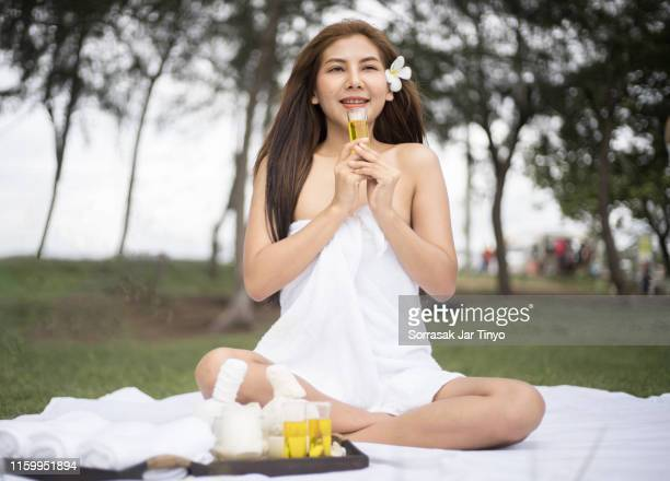 young women smelling a massage oil with the massage equipment at the outdoor spa - massage oil stock pictures, royalty-free photos & images