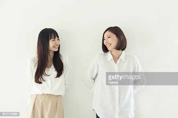 young women smiling face to face by wall - two people ストックフォトと画像