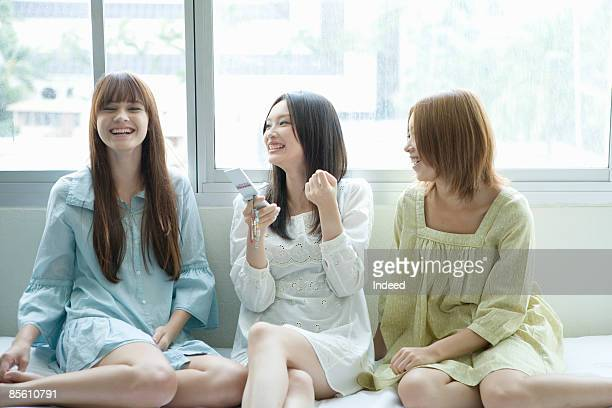 Young women smiling on bed side by side