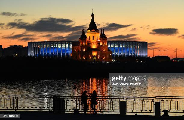 Young women stand in front of the Nizhny Novgorod stadium situated behind the cathedral of Alexandr Nevskiy in the city of Nizhny Novgorod, during...