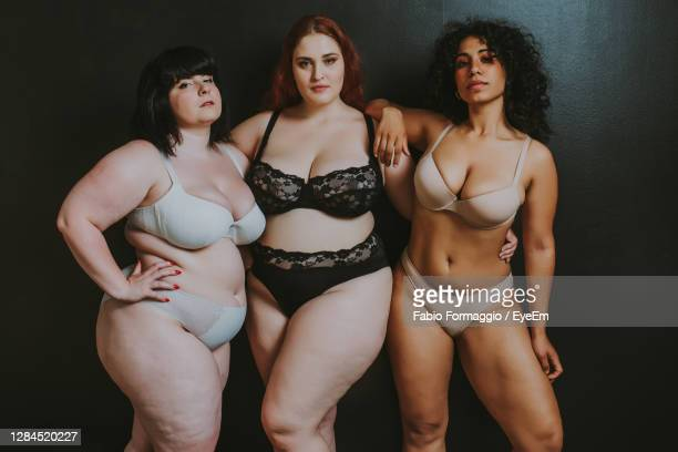 young women standing against black background - パンティー ストックフォトと画像
