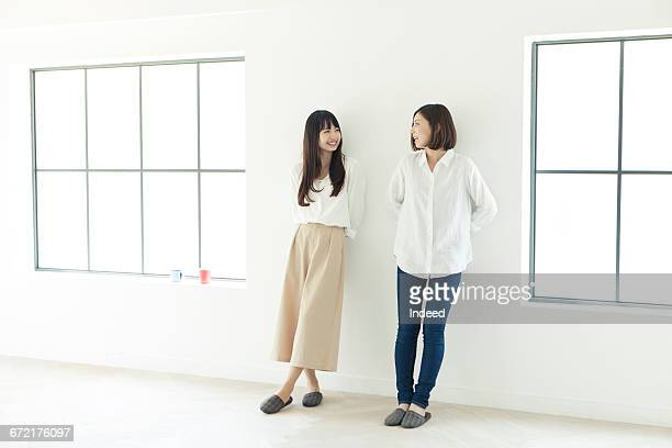 Young women standing by wall
