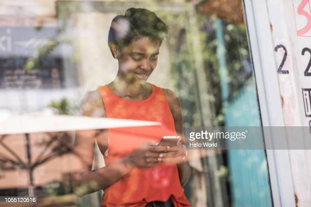 Young women standing in front of window typing on smart phone