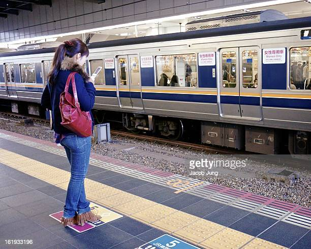 "Young women, standing on a ""Women Only"" marker, looks at her mobile phone as she waits for a train at newly-renovated Osaka Station. Across the..."